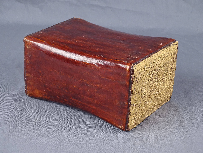 Ancien et bel oreiller de fumeur en cuir laqué rouge. Les extrémités sont...